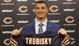 Chicago Bears' first round draft pick quarterback Mitchell Trubisky, from North Carolina, poses with a Bears' jersey during an NFL football news conference Friday, April 28, 2017, in Lake Forest , Ill. (AP Photo/Charles Rex Arbogast)