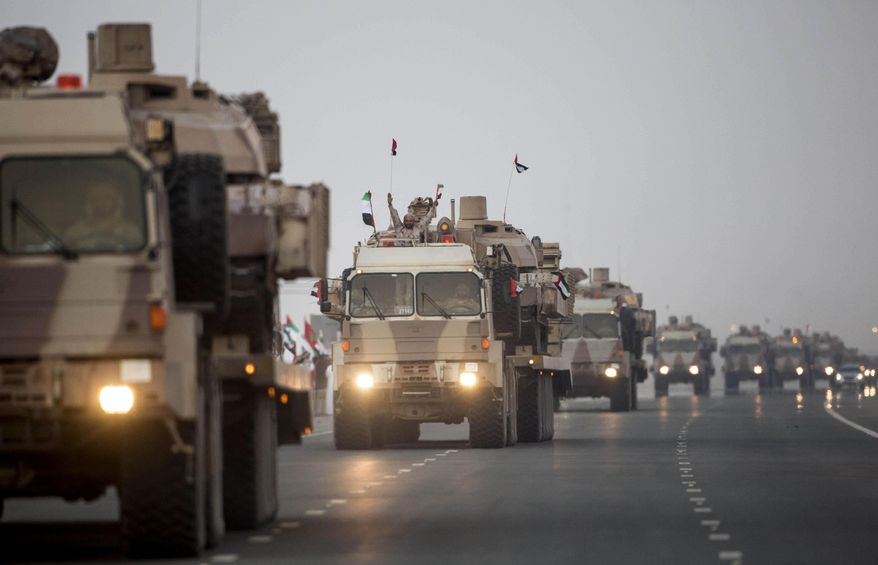 FILE- In this Nov. 7, 2015 file photo, made available by the Emirates News Agency, WAM, a convoy of UAE military vehicles and personnel travels from Al Hamra Military Base to Zayed Military City, marking the return of the first batch of UAE Armed Forces military personnel from Yemen, in Abu Dhabi, United Arab Emirates. The UAE is better known for its skyscrapers and pampered luxuries, but its battle-hardened military that's gained on-the-ground experience in the last decades is expanding into new bases in Africa. (Ryan Carter-Crown Prince Court - Abu Dhabi/WAM via AP)