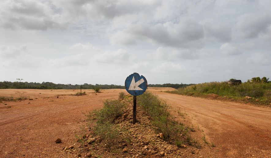 ADVANCE FOR RELEASE SATURDAY, APRIL 29, 2017, AT 3:01 A.M. EDT - This March 10, 2017, photo shows the Red bauxite runs that for miles along the path to the now shuttered mining and mill operations that once made Suralco one of Surinam's largest employers. The company, a subsidiary of Alcoa, has promised to remediate the land upon their departure of the country. (Stephanie Strasburg/Pittsburgh Post-Gazette via AP)
