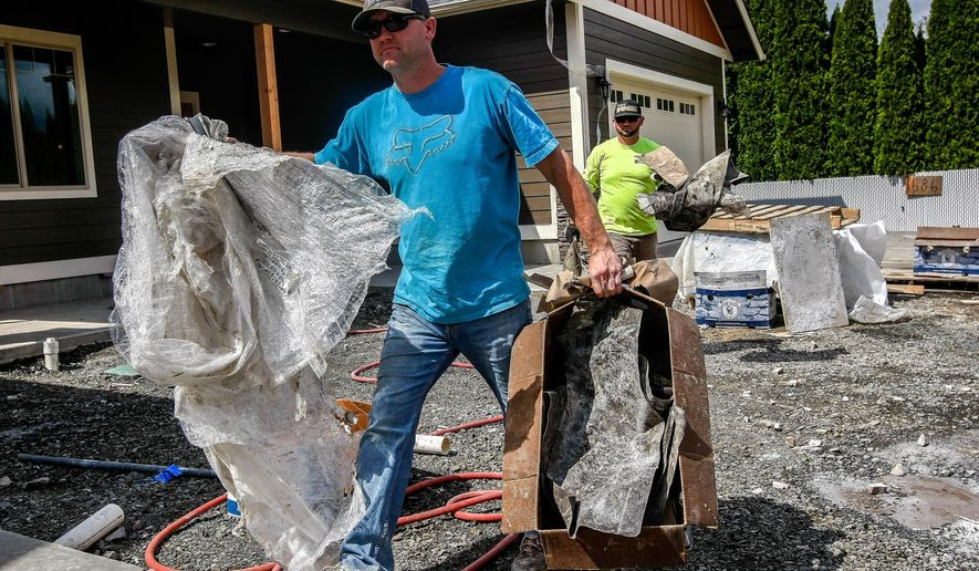 In this April 13, 2017, photo,  Leon Roberson of Leon Roberson Construction, left, and Cody Ferrano, haul debris from two spec homes near completion at the end of Primrose Lane in Roseburg, Ore. After the 2007 housing market crash, many skilled workers left Douglas County to find work elsewhere, placing people such as Edwards in high demand. (Mike Henneke/The News-Review via AP)