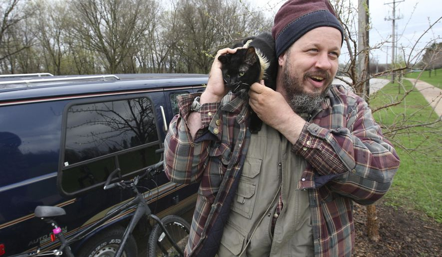 Corey Jacob plays with his cat, Nighty, outside the van he has been sleeping in, Tuesday April 18, 2017 in Rochester, Minn. Pulling together all of his resources, Jacob got the van in March. A drunk driver slammed into the van a few nights ago while it was parked disabling it.   (Ken Klotzbach/The Rochester Post-Bulletin via AP)