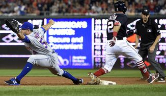 Washington Nationals' Adam Eaton (2) is safe at first against New York Mets first baseman T.J. Rivera (54) during the ninth inning of a baseball game, Friday, April 28, 2017, in Washington. Eaton was injured on the play.  (AP Photo/Nick Wass)