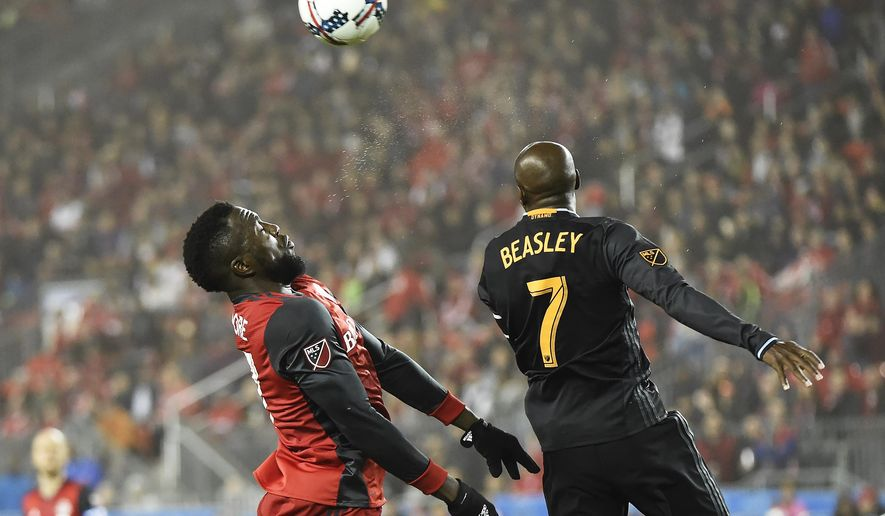 Toronto FC forward Jozy Altidore, left, and Houston Dynamo midfielder DaMarcus Beasley (7) jump for the ball during the second half of an MLS soccer match in Toronto on Friday, April 28, 2017. (Nathan Denette/The Canadian Press via AP)