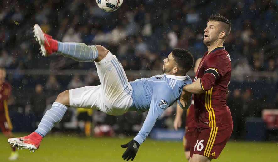Sporting Kansas City forward Dom Dwyer (14) attempts a bicycle kick against Real Salt Lake defender (16) Chris Wingert during the first half of an MLS soccer match Saturday, April 29, 2017, in Kansas City, Kan. (Nick Tre. Smith/The Kansas City Star via AP)