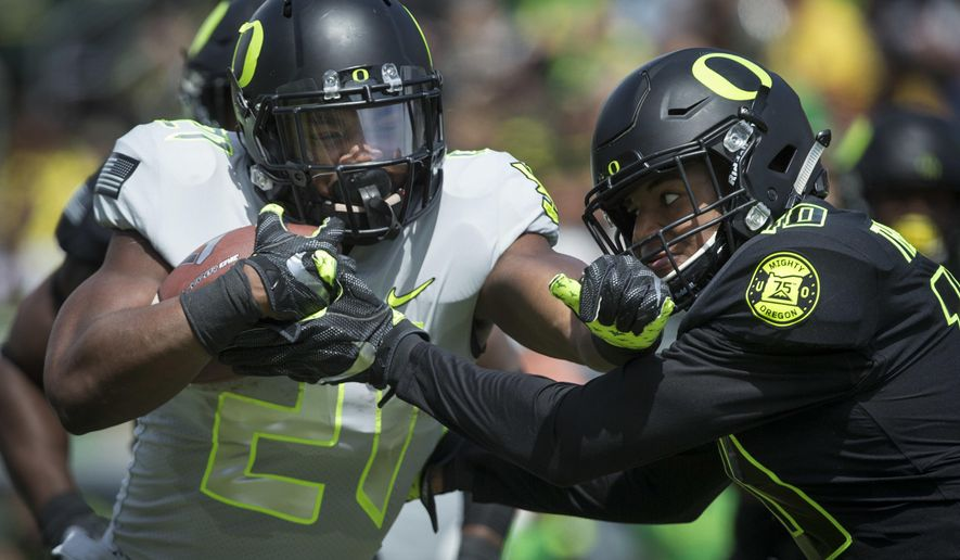 Team Free's Royce Freeman battles for yardage with Team Brave's Ty Griffin during during Oregon's spring NCAA college football game at Autzen Stadium in Eugene Ore., Saturday, April 29, 2017.  (Andy Nelson/The Register-Guard via AP)