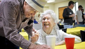 In this Saturday, April 22, 2017 photo,  Joe Lych, 85, reconnects with Arline Green, 92, both former residents of Robindale, Pa., during a reunion held at Seward fire hall in Seward, Pa. Nearly 40 years ago, the flood of 1977 destroyed the town of Robindale, Pa. (Thomas Slusser/The Tribune-Democrat via AP)