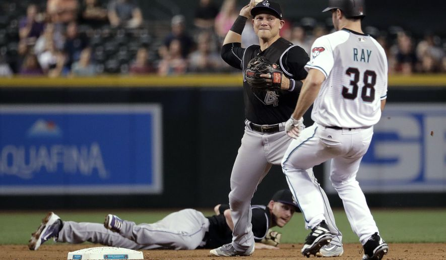 Colorado Rockies' Trevor Story watches from the ground as Arizona Diamondbacks Robbie Ray (38) is forced out by Rockies' Pat Valaika, who tried unsuccessfully to turn a double play on A.J. Pollock during the fifth inning of a baseball game, Friday, April 28, 2017, in Phoenix. (AP Photo/Matt York)