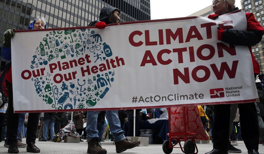 Demonstrators march against President Trump and his environmental policies during an Earth Day rally in Chicago. (AP Photo/Nam Y. Huh)