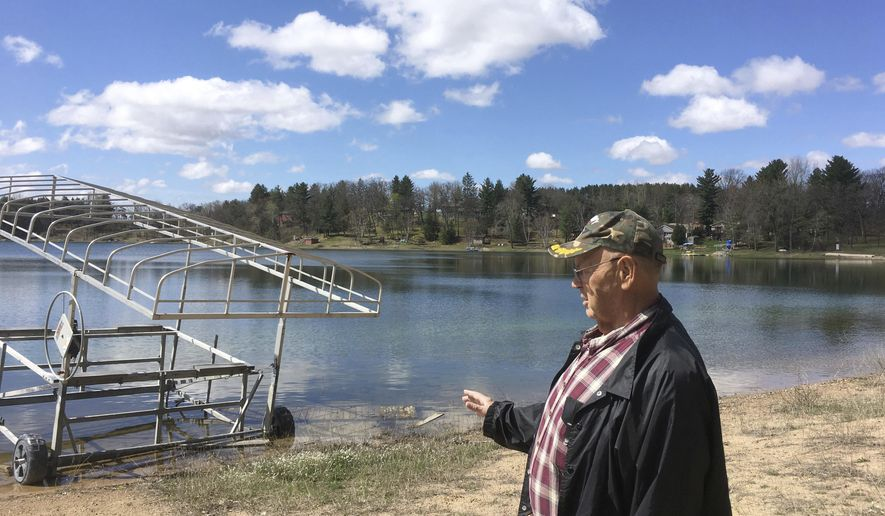 In this April 21, 2017 photo, Cris Van Houten explains how the shoreline of Huron Lake, has receded over the years in Oasis, Wisc. Van Houten and other central Wisconsin lake property owners insist a proliferation of high-capacity wells are draining the region's lakes. (AP Photo/Todd Richmond)