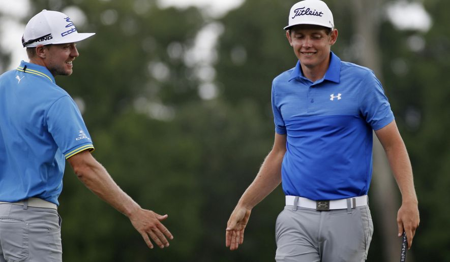 Jonas Blixt, left, of Sweden, congratulates teammate Cameron Smith, of Australia, after they birdied the 18th hole during the third round of the PGA Zurich Classic golf tournament's new two-man team format at TPC Louisiana in Avondale, La., Saturday, April 29, 2017. The pair finished the day in the lead at 19 under par. (AP Photo/Gerald Herbert)