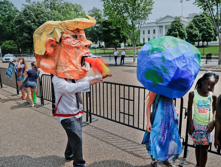 Demonstrators wearing papier-mch heads representing President Donald Trump and the planet Earth, walk along Pennsylvania Ave., in front of the White House in Washington, during a demonstration and march, Saturday, April 29, 2017. Thousands of people gather across the country to march in protest of President Donald Trump's environmental policies, which have included rolling back restrictions on mining, oil drilling and greenhouse gas emissions at coal-fired power plants. (AP Photo/Pablo Martinez Monsivais)