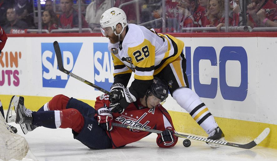 Pittsburgh Penguins defenseman Ian Cole (28) battles for the puck against Washington Capitals center Nicklas Backstrom (19), of Sweden, during the second period of Game 2 in an NHL hockey Stanley Cup second-round playoff series, Saturday, April 29, 2017, in Washington. (AP Photo/Nick Wass)