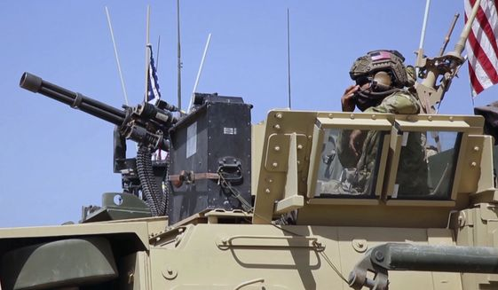 This Saturday, April. 29, 2017 still taken from video, shows an American soldier looking out of an armored vehicle in the northern village of Darbasiyah, Syria. U.S. moved troops and armored vehicles through several Syrian cities and towns on Friday and Saturday in a show of force apparently intended to dissuade Turkey and Syrian Kurdish forces from attacking each other. (AP Photo via APTV)