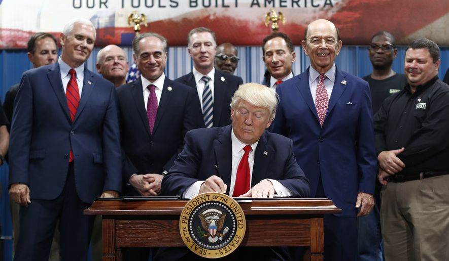 President Donald Trump, joined by Vice President Mike Pence, Secretary of Veterans Affairs David Shulkin, Secretary of Commerce Wilbur Ross, signs an Executive Order on the Establishment of Office of Trade and Manufacturing Policy at The AMES Companies, Inc., in Harrisburg, Pa., Saturday, April, 29, 2017. (AP Photo/Carolyn Kaster)