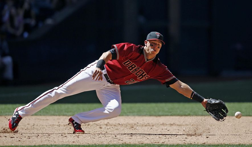Arizona Diamondbacks' Jake Lamb dives in vain for a ground ball hit by Colorado Rockies' Ian Desmond during the fifth inning of a baseball game Sunday, April 30, 2017, in Phoenix. (AP Photo/Ross D. Franklin)