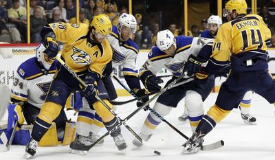 Nashville Predators right wing James Neal (18) and defenseman Mattias Ekholm (14), of Sweden, battle St. Louis Blues defenseman Carl Gunnarsson (4), also of Sweden, and right wing Ryan Reaves (75) for the puck during the second period in Game 3 of a second-round NHL hockey playoff series Sunday, April 30, 2017, in Nashville, Tenn. (AP Photo/Mark Humphrey)