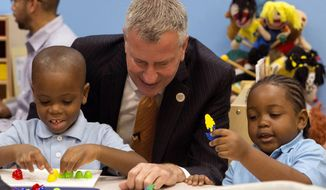 FILE - In this Sept. 4, 2014, file photo, New York Mayor Bill de Blasio visits the Inner Force Early Tots Childhood Learning Center, a community-based organization that's part of the pre-K program, in the Brooklyn borough of New York on the first day of the mayor's expansion of early childhood education. Free school for 4-year-olds was de Blasio's signature issue during his successful run for mayor in 2013. Facing re-election he has announced an ambitious plan to expand the effort to 3-year-olds. (Theodore Parisienne/The Daily News via AP, Pool, File)