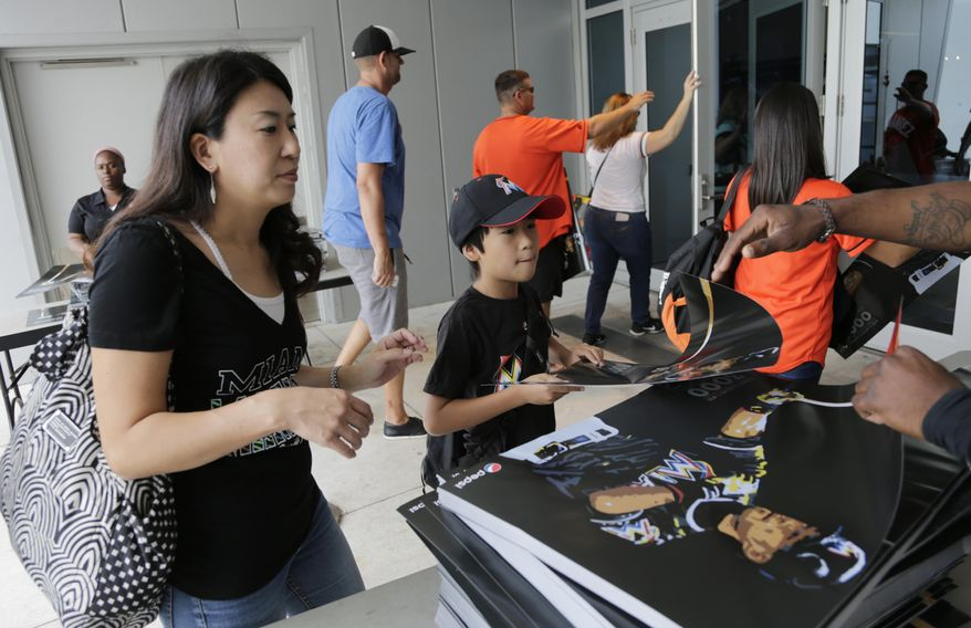 Baseball fans receive posters of Miami Marlins right fielder Ichiro Suzuki as they arrive for a baseball game between the Miami Marlins and Pittsburgh Pirates, Sunday, April 30, 2017, in Miami. Suzuki is being honored Sunday for getting his 3,000th hit in 2016. (AP Photo/Lynne Sladky)