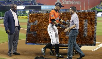 Miami Marlins' Ichiro Suzuki, center, shakes hands with club president David Samson, right, as Michael Hill, president of baseball operations, looks on during a pregame ceremony honoring Ichiro's 3,000th career hit before a baseball game against the Pittsburgh Pirates, Sunday, April 30, 2017, in Miami. (AP Photo/Lynne Sladky)