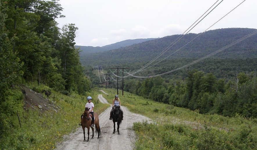 In this undated photo two people ride horses along power lines owned by the Vermont Electric Power Company where they run through wildlife areas in Ferdinand, VT. National Grid has proposed construction of new electric transmission lines alongside these existing lines that would carry Canadian power through northeastern Vermont to southern New England reopening the long-settled conservation easements governing the use of the land the new lines would traverse. (AP Photo/Wilson Ring)