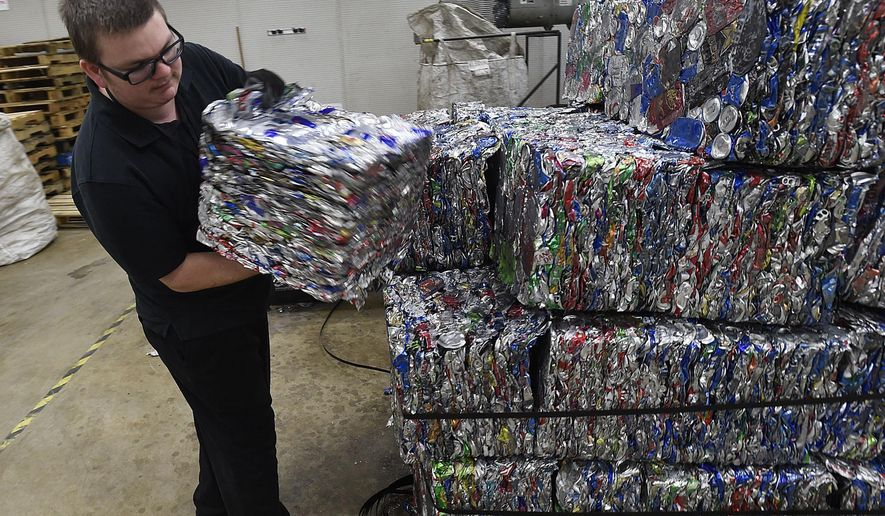In this Thursday, April 20, 2017 photo, Duane Gay, onsite supervisor of the Albany, Oregon's BottleDrop redemption center, shows a bundle containing more than 700 compacted cans. The center has nearly doubled its intake of recycled cans and bottels. (Mark Ylen/Albany Democrat-Herald via AP)
