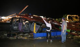 Ernestine Cook of Canton, Texas, points out the damage to spotter Michael Search of Henderson, Texas, as they inspect the damage done to the I-20 Dodge dealership after a tornado hit Canton, Texas, Saturday, April 29, 2017. Cars and trucks were piled high and the service area was destroyed. (Tom Fox/The Dallas Morning News via AP)