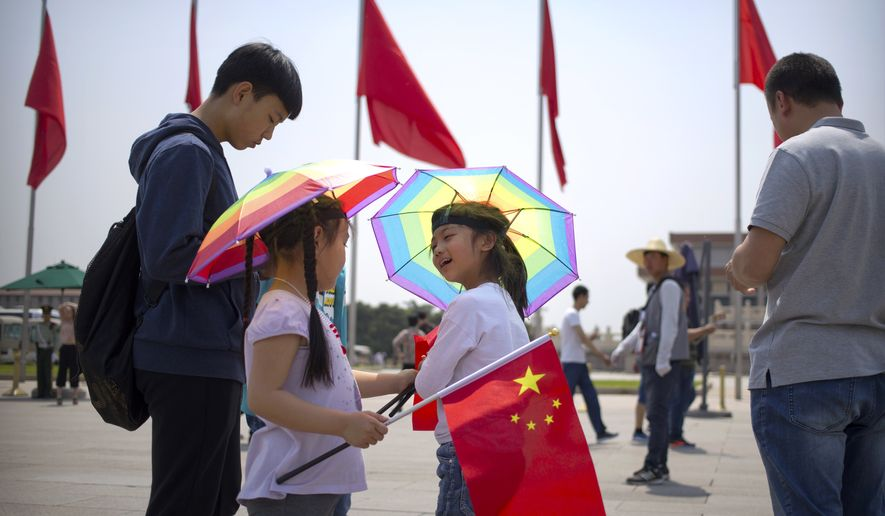Two girls wearing umbrella hats talk at each other on Tiananmen Square during the May Day holiday in Beijing, Monday, May 1, 2017. Millions of Chinese are taking advantage of the May Day holidays to visit popular tourist sites. (AP Photo/Mark Schiefelbein)