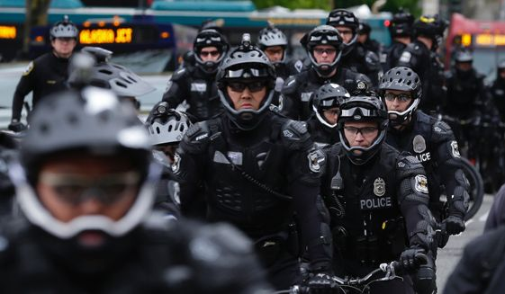 Seattle Police Officers stage near a May Day protest, Monday, May 1, 2017, in Seattle.  Immigrant and union groups marched in cities across the United States on Monday, to mark May Day and protest against President Donald Trump's efforts to boost deportations. The day has become a rallying point for immigrants in the U.S. since demonstrations were held in 2006 against a proposed immigration enforcement bill. (AP Photo/Ted S. Warren)