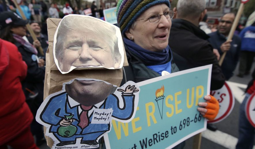 Nancy Kohn, of Boston, holds a Donald Trump puppet and a placard during a May Day rally, Monday, May 1, 2017, in Chelsea, Mass. Thousands of people chanted, picketed and marched on cities across America on Monday as May Day demonstrations raged against President Donald Trump's immigration policies. (AP Photo/Steven Senne)