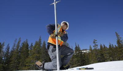 FILE- In this April 3, 2017, file photo, Tony Orozco, an hydrographer for the Pacific Gas & Electric pushes the snow survey tube into the snowpack during a PG&E snow survey near Spaulding Lake in Nevada County, Calif. State snowpack surveyors head out Monday, May 1, for the final manual measurement of the wet season. (AP Photo/Rich Pedroncelli, File)