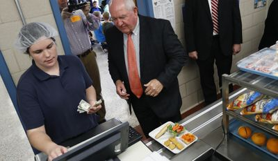 Agriculture Secretary Sonny Perdue pays for his lunch in the Catoctin Elementary School cafeteria in Leesburg, Va., Monday, May 1, 2017. After eating lunch with students Perdue unveiled a new rule on school lunches as the Trump administration and other Republicans press for flexibility after eight years of the Obama's emphasis on health eating. (AP Photo/Carolyn Kaster)