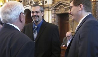 Kansas state Sen. Richard Hilderbrand, R-Baxter Springs, center, talks with state Sen. Larry Wilborn, R-McPherson, left, and former state Sen. Jake LaTurner, R-Pittsburg, right, before Hilderbrand's swearing in as a legislator Monday, May 1, 2017, in Topeka, Kan. Hilderbrand replaced LaTurner after Gov. Sam Brownback appointed LaTurner to fill a vacancy in the state treasurer's office. (AP Photo/John Hanna)