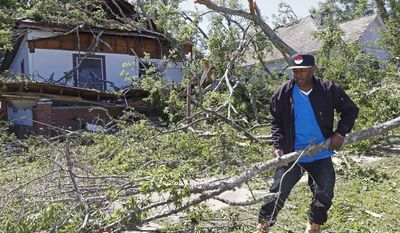 Dee Andre Johnson, 48, hauls off branches Monday, May 1, 2017, that fell on his neighbor's house Sunday morning, during a possible tornado that swept through Durant, Miss. (AP Photo/Rogelio V. Solis)