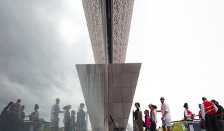 Visitors are seen reflected as they enter the Smithsonian National Museum of African American History and Cultural on the National Mall in Washington, Monday, May 1, 2017. The hottest ticket in Washington right now is for the new museum, where thousands of tickets are snapped up each month within minutes of being released, a full seven months after the museum opened. (AP Photo/Pablo Martinez Monsivais)