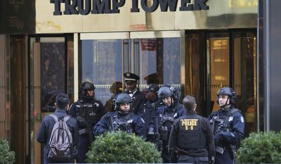 New York City Police Department officers stand at the front entrance of Trump Tower in New York. The new federal spending bill would allocate $61 million to reimburse primarily New York City and Palm Beach County for police overtime and other local expenses related to securing President Donald Trump and his family at Trump Tower and Mar-a-Lago. (AP Photo/Seth Wenig, File)