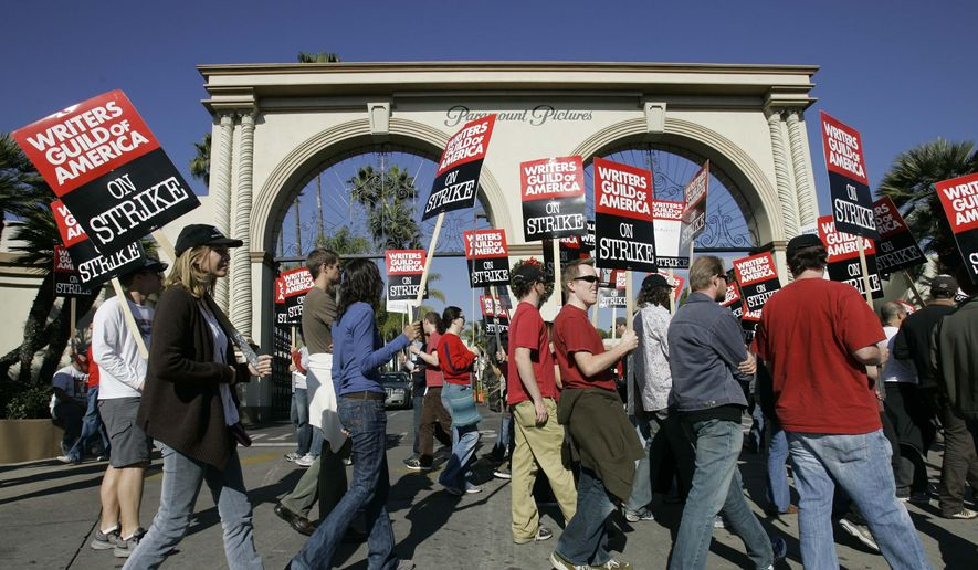In this Dec. 13, 2007, file photo, striking writers walk the picket line outside Paramount Studios in Los Angeles. (AP Photo/Nick Ut, File)