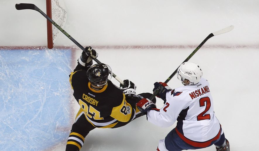 Pittsburgh Penguins' Sidney Crosby (87) takes a hit from Washington Capitals' Matt Niskanen during the first period of Game 3 in an NHL Stanley Cup Eastern Conference semifinal hockey game against the Washington Capitals in Pittsburgh, Monday, May 1, 2017. Crosby left the game and did not return. The Capitals won in overtime 3-2. (AP Photo/Gene J. Puskar)