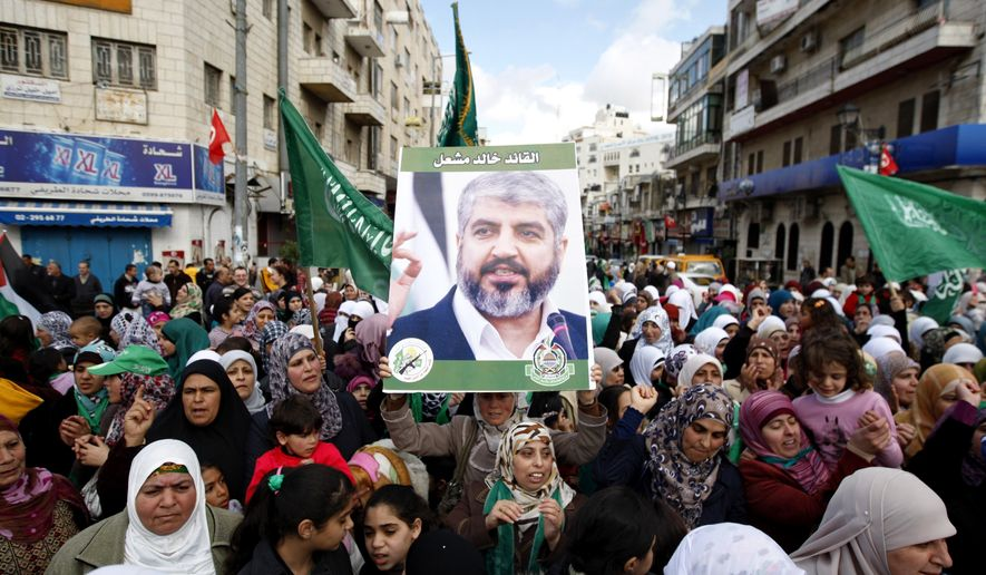 FILE -- In this Dec 14, 2012 file photo, Palestinian supporters of Hamas hold a picture of leader Khaled Mashaal, during a rally to celebrate the 25th anniversary of the militant group, in the West Bank city of Ramallah. The new political program of Hamas, published Monday, is meant to help the Islamic militant group break out of its international isolation. The manifesto does not formally replace the group's fiery 1987 founding charter, but adopts more conciliatory language, even if some goals remain unchanged _ such as the eventual liberation of all of historic Palestine, including what is now Israel.  (AP Photo/ Majdi Mohammed)