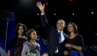 In this Nov. 7, 2012, file photo, then-President Barack Obama waves as he walks on stage with first lady Michelle Obama and daughters Malia and Sasha at his election night party in Chicago. (AP Photo/Carolyn Kaster, File)