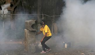 A demonstrator hides behind a barricade during clashes with the Bolivarian National Guard, at El Hatillo municipality outside Caracas, Venezuela, Tuesday, May 2, 2017. People blocked streets in Caracas with broken concrete, twisted metal and flaming piles of trash to protest the president's bid to rewrite the constitution amid a rapidly escalating political crisis.(AP Photo/Fernando Llano)