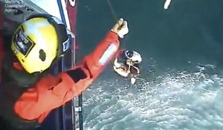 This image taken from video issued by the Maritime & Coastguard Agency on Tuesday May 2, 2017, shows the rescue of surfer Matthew Bryce. Matthew Bryce of Scotland was rescued after an intense search operation that began after his family reported him missing when he did not return from a surfing trip off the western coast of Scotland. (Maritime & Coastguard Agency via AP)