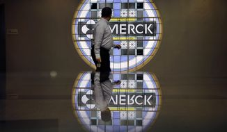 FILE - In this Thursday, Dec. 18, 2014, file photograph, a man looks back at the Merck logo on a stained glass panel at a Merck company building in Kenilworth, N.J. Merck & Company, Inc. reports earnings, Tuesday, May 2, 2017. (AP Photo/Mel Evans, File)