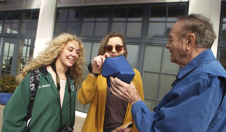 "In this image taken from video on April 5, 2017, Nathan Zaccaria, right, gets feedback from the public on a smartphone accessory he designed called the ""Shady Smart,"" in Long Branch, N.J. Zaccaria has introduced a case that fits over smartphones and keeps out the glare so that consumers can see the screens outdoors. ((Brian Johnston/The Asbury Park Press via AP)"