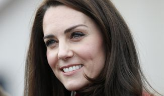 FILE - In this Sunday, Feb. 5, 2017 file photo, Britain's Kate, the Duchess of Cambridge, talks to runners as she prepares to take part in a relay race, during a training event to promote the charity Heads Together, at the Queen Elizabeth II Park in London. Three photographers have appeared in a French court on Tuesday May 2, 2017, over topless photographs of the Duchess of Cambridge, an invasion of privacy case that has outraged Britain's royal family. (AP Photo/Alastair Grant, Pool, File)