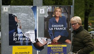 A woman walks past electoral posters of French centrist presidential candidate Emmanuel Macron, torn at left, and far-right candidate Marine Le Pen in Ascain, southwestern France, Tuesday, May 2, 2017. France vote Sunday May 7 for the second round of the presidential election. (AP Photo/Bob Edme)