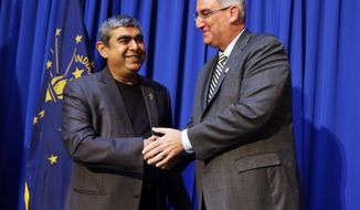 Indiana Gov. Eric J. Holcomb, right, greets Dr. Vishal Sikka, CEO of Infosys, following an announcement at the Statehouse in Indianapolis, Tuesday, May 2, 2017, plans for Infosys to increase its operations in the U.S, establishing four new state-of-the-art technology and innovation hubs in the U.S., with the first one in Indiana. (AP Photo/Michael Conroy)