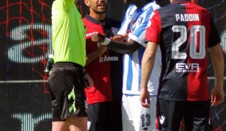 Referee Daniele Minelli shows the yellow card to Pescara's Sulley Muntari, second from right, during a Serie A soccer match between Pescara and Cagliari, at the Cagliari Sant'Elia stadium, Italy, Sunday, April 30, 2017. Pescara midfielder Sulley Muntari walked off the pitch in protest during his side's Serie A match at Cagliari after being booked for complaining to the referee about racist abuse from fans. Muntari told referee Daniele Minelli about the racist chants from home fans in the final minute of Pescara's 1-0 defeat but the official showed the Ghana midfielder a yellow card. (Fabio Murru/ANSA via AP)