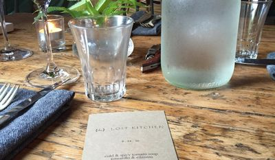 "This Aug. 24, 2016 photo shows a menu on a rustic wooden table at The Lost Kitchen in Freedom, Maine. The chef and owner Erin French got thousands of phone calls this year on April 1 when she opened reservations for the season for her 40-seat restaurant in an old mill in a tiny Maine town. French has just come out with a cookbook called ""The Lost Kitchen: Recipes and A Good Life Found in Freedom, Maine,"" telling the remarkable story of her career from a teenager working in her dad's diner to giving dinner parties in her apartment to running a successful restaurant. (AP Photo/Beth J. Harpaz)"