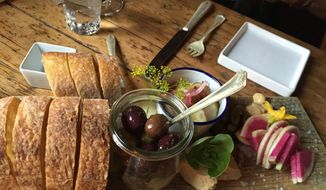 "This Aug. 24, 2016 photo shows bread, olives and other pre-dinner nibbles served at The Lost Kitchen in Freedom, Maine, before the meal begins. The chef and owner Erin French got thousands of phone calls this year on April 1 when she opened reservations for the season for her 40-seat restaurant in an old mill in a tiny Maine town. French has just come out with a cookbook called ""The Lost Kitchen: Recipes and A Good Life Found in Freedom, Maine,"" telling the remarkable story of her career from a teenager working in her dad's diner to giving dinner parties in her apartment to running a successful restaurant. (AP Photo/Beth J. Harpaz)"