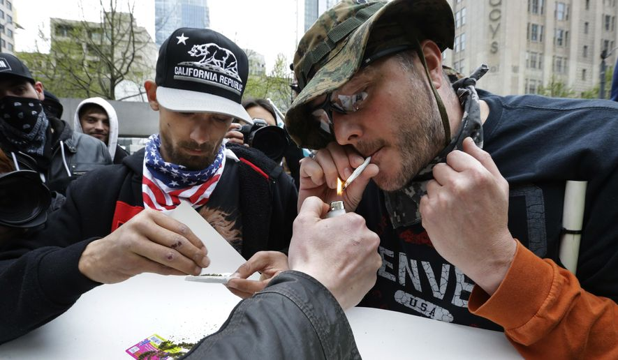 Mark Burrell, right, and a man who said he goes by the name Abundis, left, light marijuana joints Monday, May 1, 2017, during a May Day protest in Seattle. The two men identify with constitutionalist and libertarian ideals and had been arguing with counter protesters when they decided to smoke pot together with their opponents. (AP Photo/Ted S. Warren) **FILE**